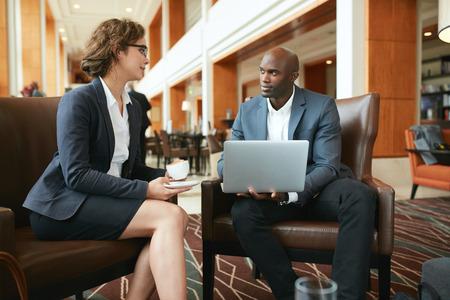 Foto de Portrait of two young business colleagues sitting at coffee shop. African businessman with laptop and businesswoman with cup of coffee discussing work. - Imagen libre de derechos