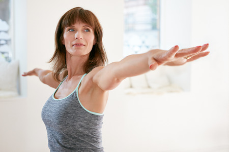 Foto de Portrait of mature woman stretching her arms and looking away at gym. Beautiful woman performing yoga in warrior pose, Virabhadrasana. - Imagen libre de derechos