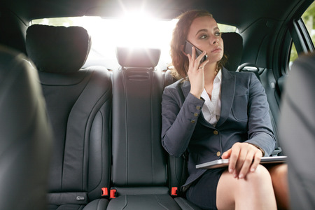 Foto de Businesswoman with mobile phone on the backseat of a car. Female associate making a phone call while travelling to work. - Imagen libre de derechos