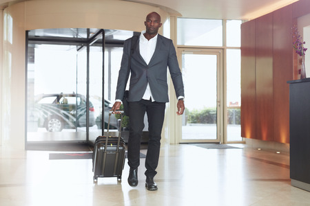 Photo for Businessman walking in hotel lobby. Full length portrait of young african executive with a suitcase. - Royalty Free Image
