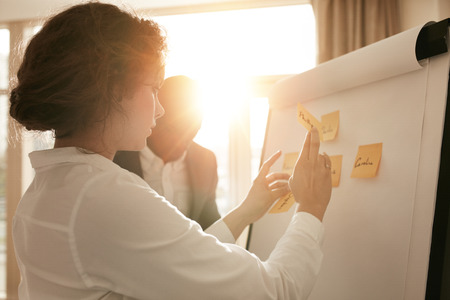Foto de Shot of young business professionals brainstorming in a meeting. Businesswoman and businessman presenting their ideas on whiteboard. - Imagen libre de derechos