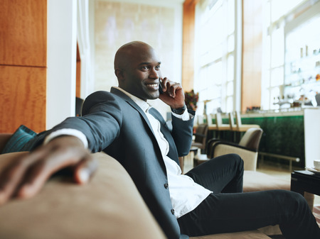 Photo pour Happy young businessman sitting relaxed on sofa at hotel lobby making a phone call, waiting for someone. - image libre de droit