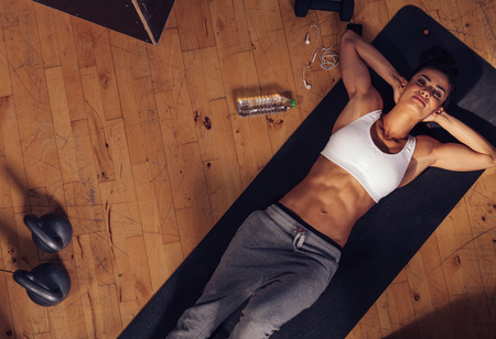 Foto de Top view of relaxing young woman lying on fitness mat. Overhead shot of female athlete resting after intense workout with water bottle, mobile phone and kettle bell on floor. - Imagen libre de derechos
