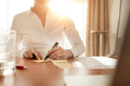 Photo for Cropped shot of woman writing some names on sticky notes while sitting in conference room. - Royalty Free Image