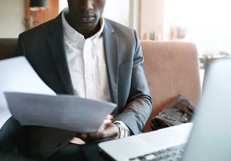 Foto de Cropped shot of young businessman going through some paperwork. African business executive reading documents while sitting at coffee shop. - Imagen libre de derechos