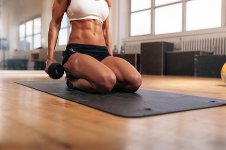 Foto de Cropped image of muscular woman exercising with dumbbells while sitting on fitness mat in gym. Focus on abs. - Imagen libre de derechos