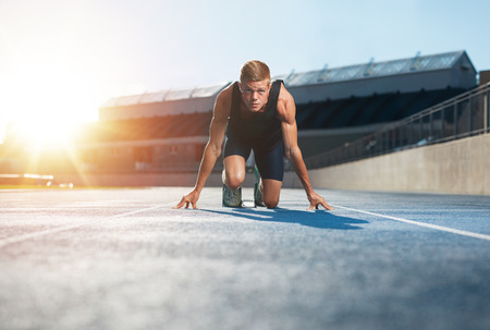 Photo pour Young man athlete in starting position ready to start a race. Male sprinter ready for a run on racetrack looking at camera with sun flare. - image libre de droit