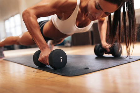 Photo pour Muscular woman doing push-ups on dumbbells in gym. Powerful female exercising in health club. - image libre de droit
