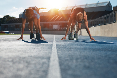 Photo pour Sprinters at starting blocks ready for race . Athletes at starting position on athletics stadium race track with sun flare. - image libre de droit