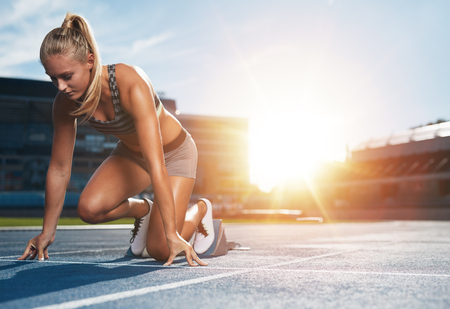 Foto de Young woman athlete at starting position ready to start a race. Female sprinter ready for sports exercise on racetrack with sun flare. - Imagen libre de derechos