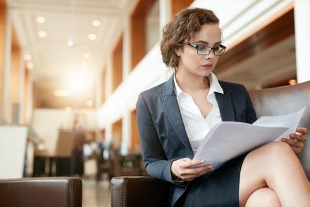 Foto de Portrait of businesswoman reading document. Female professional in hotel lobby examining papers. - Imagen libre de derechos