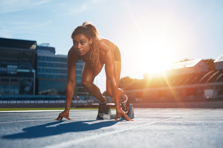 Foto de Confident female athlete in starting position ready for running. Young woman about to start a sprint looking away with bright sunlight from behind. - Imagen libre de derechos