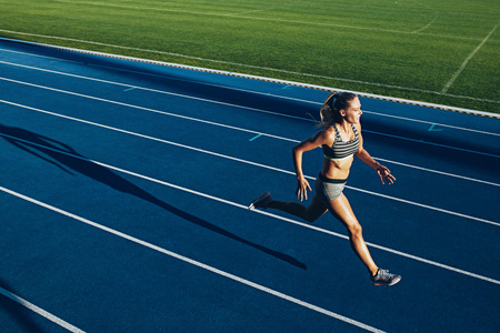 Foto de Young woman running on racetrack during training session. Female runner practicing on athletics race track. - Imagen libre de derechos
