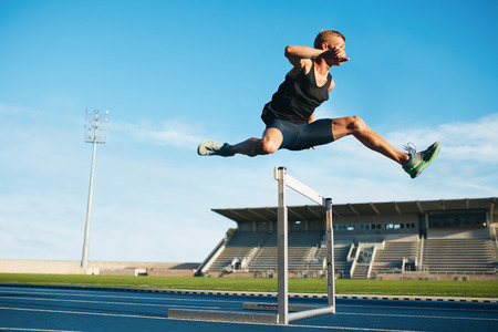 Foto de Professional male track and field athlete during obstacle race. Young athlete jumping over a hurdle during training on racetrack in athletics stadium. - Imagen libre de derechos