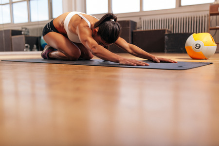 Foto de Shot of a young woman doing yoga on the gym floor. Muscular female doing stretching workout at health club. - Imagen libre de derechos