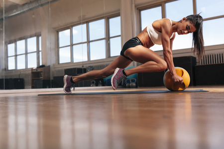 Foto de Woman doing intense core exercise on fitness mat. Muscular young woman doing workout at gym. - Imagen libre de derechos