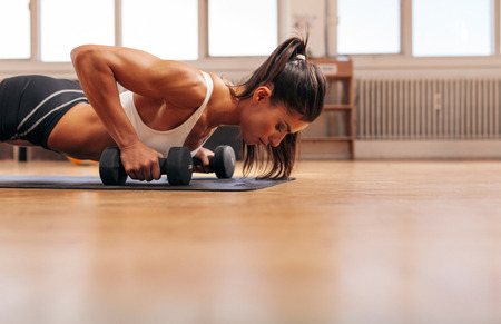 Foto de Strong young woman doing push-ups on dumbbells in gym. Fit female exercising in health club with copy space. - Imagen libre de derechos