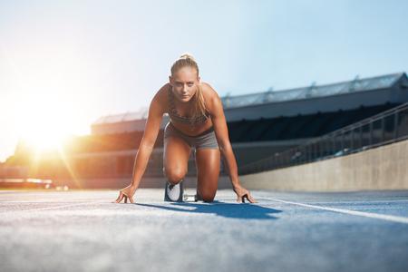 Foto de Confident young female athlete in starting position ready to start a sprint. Woman sprinter ready for a run on racetrack with sun flare. - Imagen libre de derechos