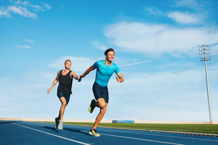 Photo for Shot of professional male athletes passing over the baton while running on the track. Athletes practicing relay race on racetrack. - Royalty Free Image
