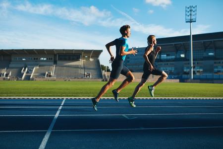 Foto de Two young men running on race track. Male professional athletes running on athletics race track. - Imagen libre de derechos