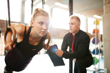 Foto de Fit young woman with her personal fitness trainer in the gym exercising with gymnastic rings - Imagen libre de derechos