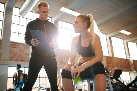Photo pour Young woman sitting on a stool and discussing exercise plan with personal trainer. Trainer making an fitness plan for young female client at gym. - image libre de droit