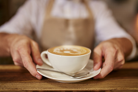 Foto de Close up of man serving coffee while standing in coffee shop. Focus on male hands placing a cup of coffee on counter. - Imagen libre de derechos