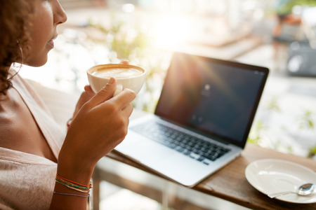 Foto de Cropped image of woman drinking coffee with a laptop on table at a restaurant. Young girl holding a cup of coffee at cafe. - Imagen libre de derechos