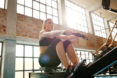 Photo pour Young caucasian woman doing exercises on fitness machine in gym. Female using rowing machine at  fitness club. - image libre de droit