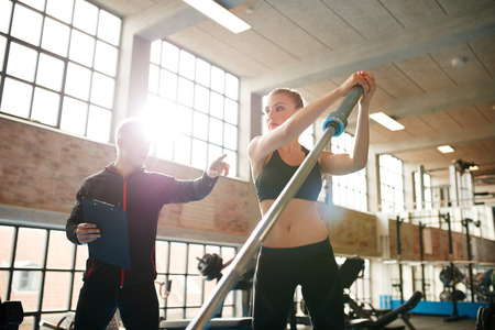 Foto de Fitness woman exercising with fitness trainer in gym. Female working out with her personal trainer at health club. - Imagen libre de derechos