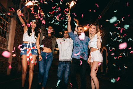 Foto de Group of young people having a party, outdoors. Multiracial young men and women celebrating with confetti. Best friend having party at night. - Imagen libre de derechos