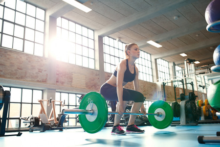 Foto de Young woman working hard in the gym. Fit female athlete lifting weights in health club. - Imagen libre de derechos