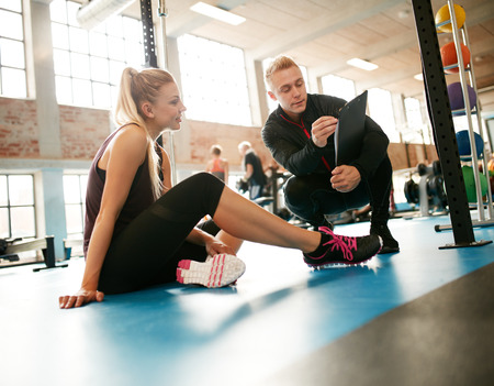 Photo pour Personal trainer helping young woman on her work out routines in gym. Female sitting on floor with her personal trainer showing fitness report on a clipboard. - image libre de droit