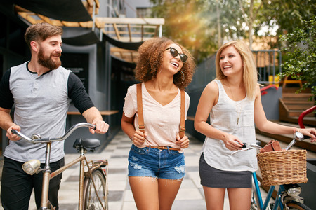 Photo for Happy young people walking down the city street with their bicycles and smiling. Young man and women on road with their bikes. - Royalty Free Image