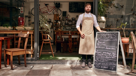 Foto de Portrait of young man standing at the entrance of his coffee shop with a black board. Barista standing in the doorway of a restaurant. - Imagen libre de derechos