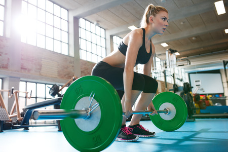 Photo pour Muscular caucasian woman in a gym doing heavy weight exercises. Young woman doing weight lifting at health club. - image libre de droit