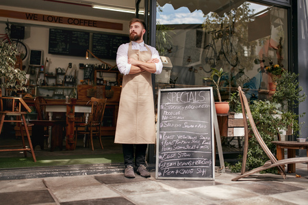 Foto de Full length shoot of a young waiter standing in door of a cafe. Young man with beard wearing an apron  standing with her arms crossed and looking away. - Imagen libre de derechos