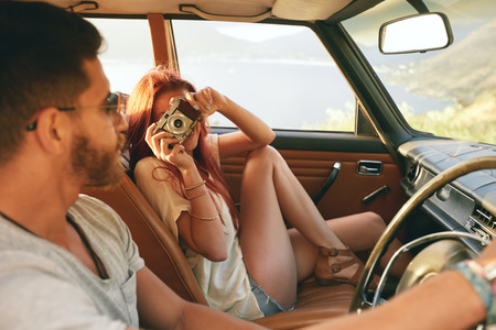 Photo pour Caucasian couple going on a road trip. Woman taking pictures with camera and man driving car. - image libre de droit