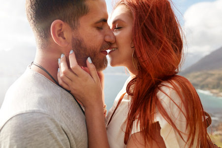 Photo pour Close up shot of affectionate young couple embracing and kissing outdoors. - image libre de droit