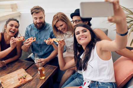 Photo for Group of friends taking selfie on a smart phone. Young people eating pizza on rooftop party taking selfie. - Royalty Free Image