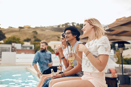 Photo for Happy young friends sitting by the pool having cocktail. Young people relaxing by the swimming pool with their feet in water during a party. Men and women enjoying rooftop party. - Royalty Free Image