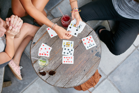 Photo for Top view of three young friends playing cards at cafe. Young people playing card game at coffee shop. - Royalty Free Image