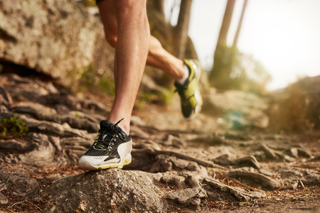 Photo pour Close-up of trail running shoe on challenging rocky terrain. Male runner's legs working out on extreme terrain outdoors. - image libre de droit