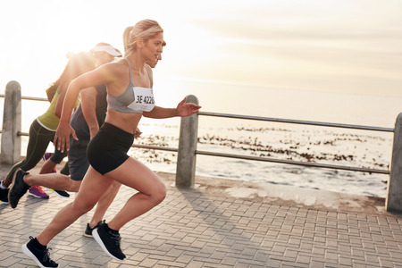 Foto per Portrait of young people running on seaside promenade. Group of women running marathon. - Immagine Royalty Free
