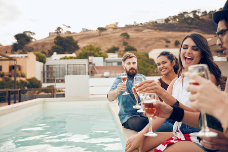 Photo pour Outdoor shot of happy group of young people sitting on the edge of the pool drinking wine. Multiracial friends enjoying and toasting drinks during a rooftop party. - image libre de droit