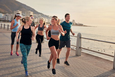 Foto per Portrait of young runners enjoying workout on the sea front path along the shoreline.  Running club group running along a seaside promenade. - Immagine Royalty Free