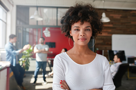 Foto de Portrait of woman standing in busy creative office looking at camera. Attractive female creative professional in design studio. - Imagen libre de derechos