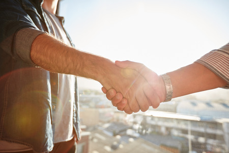 Photo for Closeup of two shaking male hands with sun flare. Focus on handshake against cityscape. - Royalty Free Image