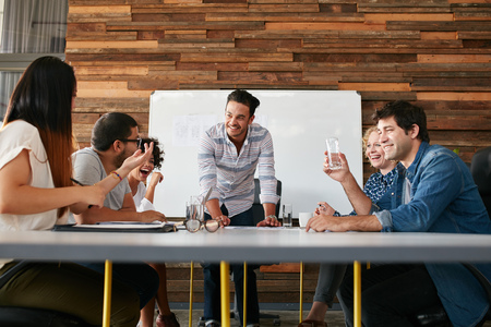 Foto de Group of happy young people having a business meeting. Creative people sitting at table in boardroom with man explaining business strategy. - Imagen libre de derechos