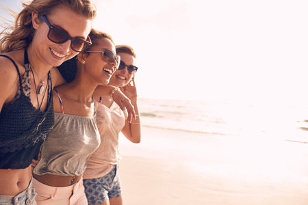 Foto de Group of beautiful young women strolling on a beach. Three friends walking on the beach and laughing on a summer day, enjoying vacation. - Imagen libre de derechos